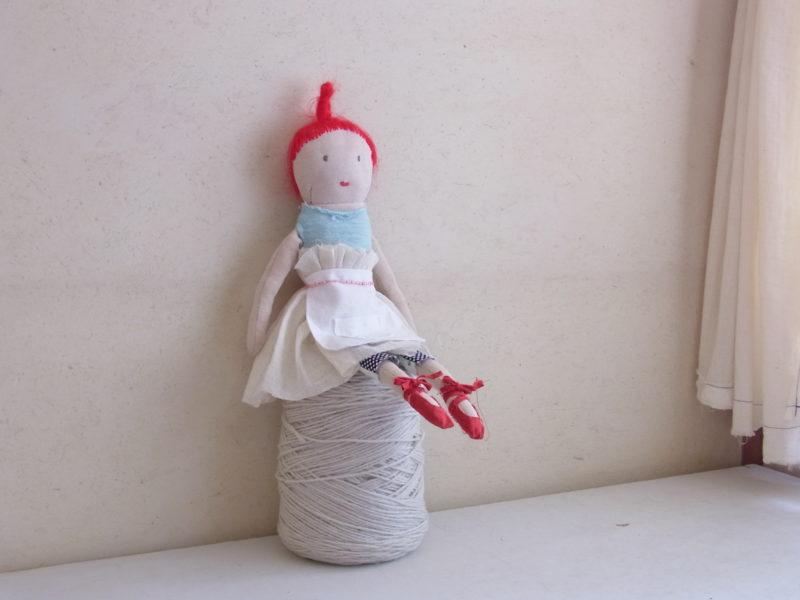 毛糸玉に座った、ハンドメイドのお人形